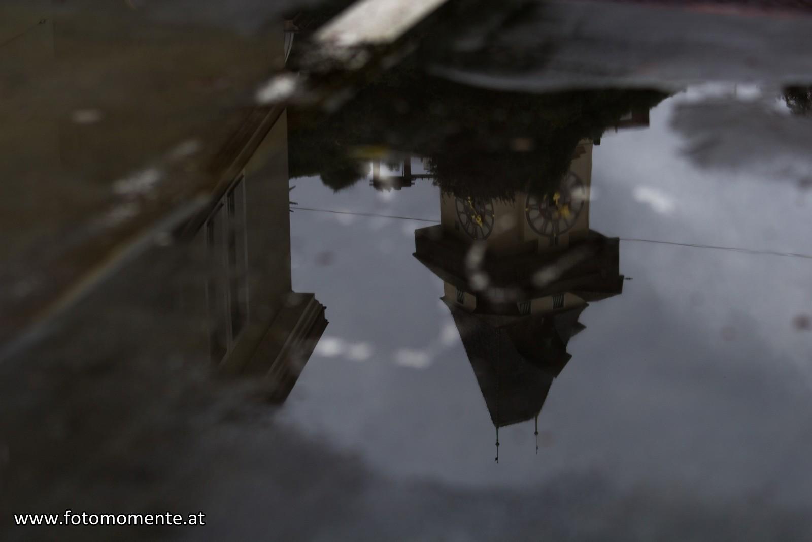 Uhrturmspiegelung in Regenpfütze